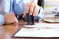 Close-up of businessman hand pressing a stamp on document in the office Royalty Free Stock Photography
