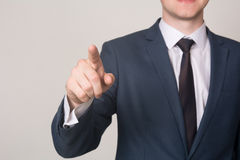 Close-up businessman hand pushing screen on light background.  Royalty Free Stock Photos