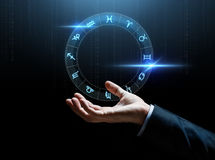 Close up of businessman hand with signs of zodiac. Astrology, horoscope, business and people concept - close up of businessman hand with signs of zodiac over stock photo