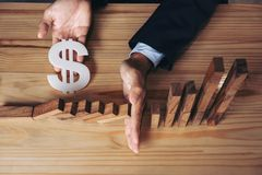 Close up of businessman hand Stopping Falling wooden Dominoes effect from continuous toppled or risk, strategy and successful int. Ervention concept for business royalty free stock image