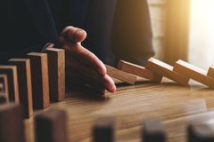 Close up of businessman hand Stopping Falling wooden Dominoes effect from continuous toppled or risk, strategy and successful int. Ervention concept for business royalty free stock images