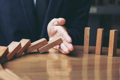 Close up of businessman hand Stopping Falling wooden Dominoes ef. Fect from continuous toppled or risk, strategy and successful intervention concept for business Royalty Free Stock Images