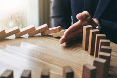 Close up of businessman hand Stopping Falling wooden Dominoes ef. Fect from continuous toppled or risk, strategy and successful intervention concept for business Stock Photos