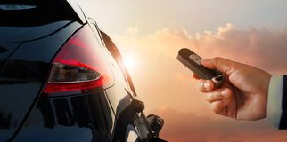 Close up businessman hand unlocked the car with remote control. On parking sunset background stock photo