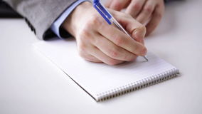 Close up of businessman hand writing to notepad stock footage