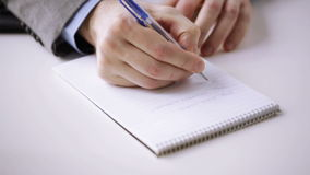 Close up of businessman hand writing to notepad stock video footage