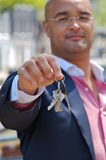 Close up of businessman handing over his keys Stock Image