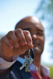 Close up of businessman handing over his keys Royalty Free Stock Image