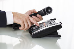 Close up of businessman hands dialing out on a black deskphone Royalty Free Stock Image
