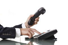 Close up of businessman hands dialing out on a black deskphone Stock Image