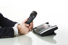 Close up of businessman hands dialing out on a black deskphone Royalty Free Stock Photo