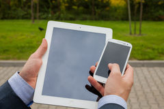 Close up of businessman hands with mobile phone and tablet pc on Royalty Free Stock Photos