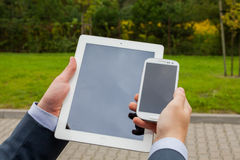 Close up of businessman hands with mobile phone and tablet pc on Stock Image