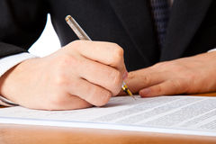Close up on a businessman hands signing a contract. Isolated on white background Stock Image