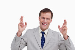 Close up of businessman with his fingers crossed. Close up of smiling businessman with his fingers crossed against a white background Royalty Free Stock Photography