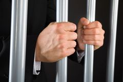 Close-up of businessman holding bars in jail Stock Image