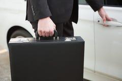 Close up of businessman holding a car door handles Stock Image