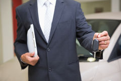 Close up of businessman holding car key and clipboard Stock Image