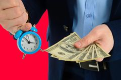Close up of businessman holding a clock and one stack of cash in hand, time and money concept. Making right decision. Close up of businessman holding a clock Stock Image