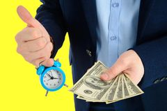 Close up of businessman holding a clock and one stack of cash in hand, time and money concept. Thumbs up. Close up of businessman holding a clock and one stack Stock Image