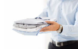 Close up of businessman holding folded shirts Stock Image