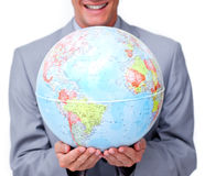 Close-up of a businessman holding a globe. Close-up of a businessman holding a terrestrial globe against a white background royalty free stock photo