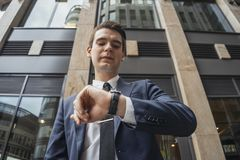 Close up of businessman holding mobile phone in hand and looking at watches. royalty free stock photography