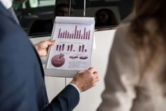 Car Salesman Holding Graphs. Close up of businessman holding statistics graph with payment plan while selling cars in showroom Stock Photography