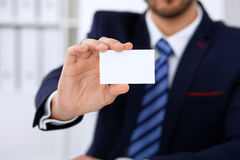Close up of  businessman or lawyer  giving a business card while sitting at the table. He offering partnership and succe Royalty Free Stock Photos
