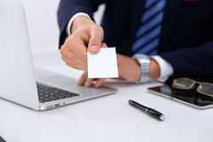 Close up of  businessman or lawyer  giving a business card while sitting at the table. He offering partnership and succe Stock Photography