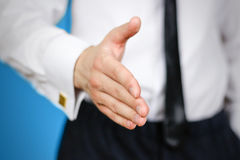 Close up. Businessman offering handshake to you. The man holds o Royalty Free Stock Images