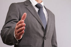 Close up of businessman with open hand ready to seal a deal gesturing a hand shake. Meeting new business partners, partnership, ne Stock Photography