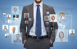 Close up of businessman over icons with contacts. Corporate business, people and cooperation concept - close up of businessman over blue background with icons of stock photography