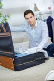 Close up businessman packing clothes into travel bag Royalty Free Stock Images
