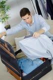Close up businessman packing clothes into travel bag Stock Photos