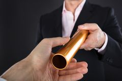Businessman Passing A Golden Relay Baton. Close-up Of A Businessman Passing Golden Relay Baton To Colleague stock photo
