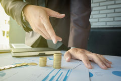 Close-up of Businessman pointing coin to rising stack of coins. Close up of Businessman pointing coin to rising stack of coins stock image