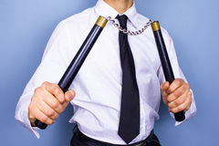 Businessman with nunchucks. Close up of a businessman posing with nun chucks Stock Image
