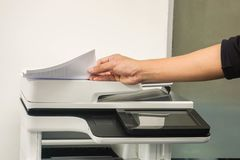 Businessman pull printing documents from office multifuntion printer. Close up businessman pull printing documents from office multifuntion printer stock photos