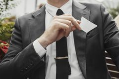 Close up of businessman putting blank business card in his black jacket pocket. stock image