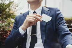 Close up of businessman putting blank business card in his blue jacket pocket. stock image