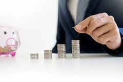 Close up of Businessman putting coin into small piggy bank , The Royalty Free Stock Photography