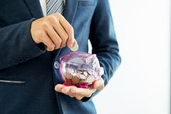 Close up of Businessman putting coin into small piggy bank , The. Concept of saving money and investment Stock Photography