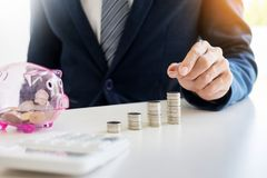 Close up of Businessman putting coin into small piggy bank , The. Concept of saving money and investment Royalty Free Stock Images
