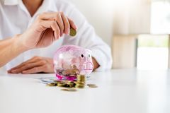 Close up of Businessman putting coin into small piggy bank , The. Concept of saving money and investment Stock Photo