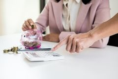 Close up of Businessman putting coin into small piggy bank , The. Concept of saving money and investment Royalty Free Stock Image