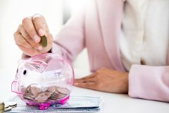 Close up of Businessman putting coin into small piggy bank , The. Concept of saving money and investment Stock Photos