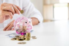 Close up of Businessman putting coin into small piggy bank , The. Concept of saving money and investment Royalty Free Stock Photos