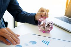 Close up of Businessman putting coin into small piggy bank , The Stock Photos