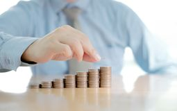Businessman Putting Coin To Rising Stack Of Coins. Close-up Of Businessman Putting Coin To Rising Stack Of Coins royalty free stock image